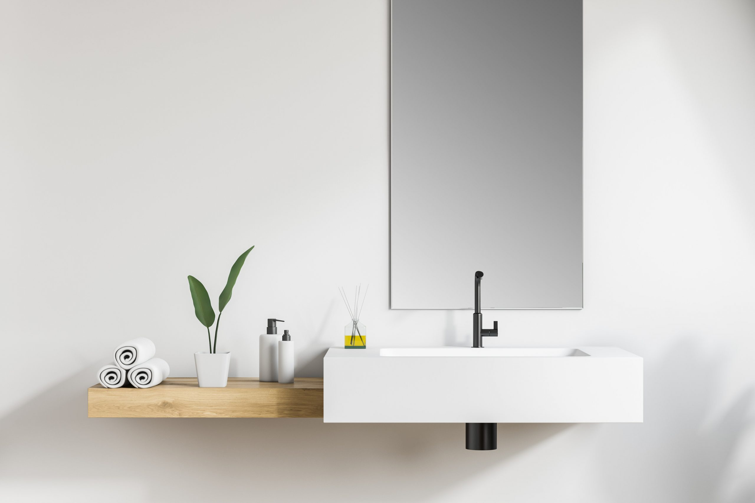 Interior of white bathroom with angular white sink, narrow mirror above it and wooden shelf with rolled towels and creams. 3d rendering